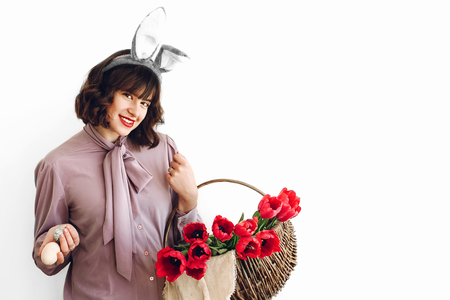 easter hunt concept. beautiful stylish girl in bunny ears holding basket with pink tulips and colored easter eggs on white background isolated. happy child looking for eggs. space for text