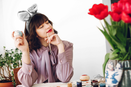 happy easter concept. beautiful stylish girl in bunny ears smiling and painting easter eggs on rustic table with tulips and paint in home with space for text. woman relaxing. easter hunt
