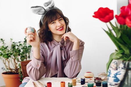 beautiful stylish girl in bunny ears smiling and painting easter eggs on rustic table with tulips and paint in home with space for text. woman  having fun. easter hunt