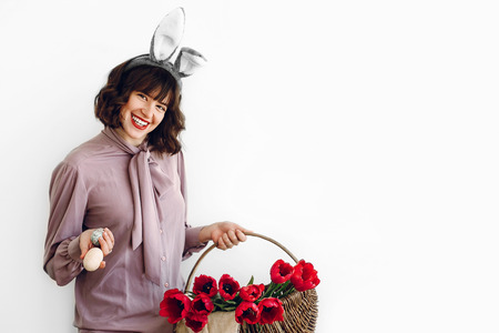 happy Easter. beautiful stylish girl in bunny ears holding basket with easter eggs and  pink tulips on white background isolated. easter hunt concept. happy woman holding painted egg