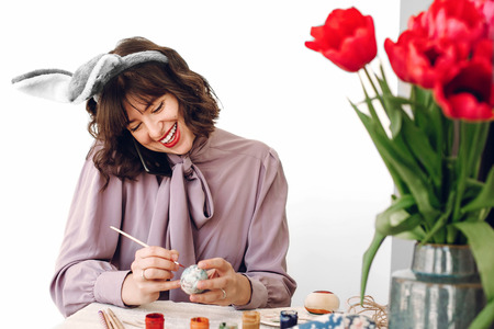beautiful stylish girl in bunny ears smiling and painting easter eggs on rustic table with colorful paint and tuilips in home with space for text. woman talking on phone, easter greetings