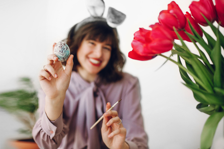 easter hunt. beautiful stylish girl in bunny ears smiling and painting easter eggs on rustic table with tulips and paint in home with space for text. woman showing egg and having fun.