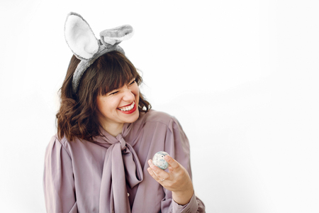 beautiful stylish girl in bunny ears holding easter egg with funny emotions and smiling on white background isolated with space for text. funny easter hunt concept. happy woman