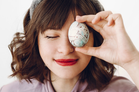 beautiful stylish girl in bunny ears holding easter egg at eyes and relaxing on white background with space for text. funny easter hunt concept. happy easter celebration