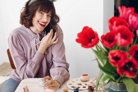 happy easter greetings. beautiful stylish girl in bunny ears smiling and painting easter eggs on rustic table with colorful paint and tuilips in home with space for text. woman talking on phone