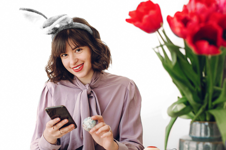 beautiful stylish girl in bunny ears smiling and painting easter eggs on rustic table and holding phone in home with space for text. woman talking photo of easter table. easter hunt Standard-Bild