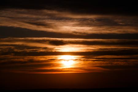 素晴らしい夕日の壁紙。オレンジ色の空に美しい赤い夕日と雲、ドラマチックな景色。魅力的なイメージ。美しい自然の瞬間、息をのむような風景