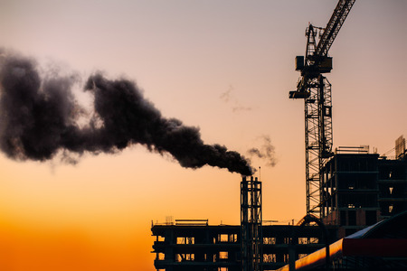Atmospheric air pollution from industrial smoke. Crane and building construction site with pipe with smoke on background of sunset sky. Environmental problem of city air pollution