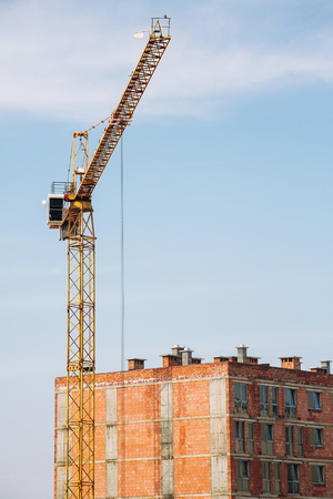 Crane and building construction site on background of  sky. Industrial landscape with silhouettes of cranes and building bricks over sunlight. space for text . steel and concrete . development Banque d'images