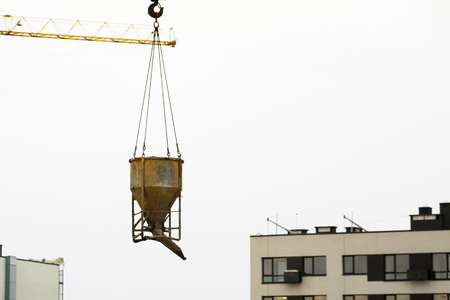 crane lifting bucket of cement and transporting at construction site at new building skyscrapers. Industrial landscape with cranes, building steel and concrete