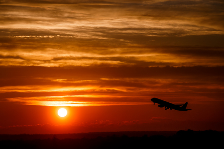 Airplane at sunset sky in the air with space for text. Silhouette of a big passenger  aircraft in sun light. transportation concept. plane flying in the dramatic sky. amazing atmospheric image Stock Photo