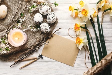 stylish painted easter egg black and white colors at rustic wooden background with spring flowers and candle. happy easter greeting card. modern easter eggs top view. holiday traditions Stock Photo