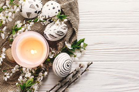stylish easter flat lay. painted easter eggs black and white colors at rustic wooden background with spring flowers and candle. happy easter greeting card. modern easter eggs top view.