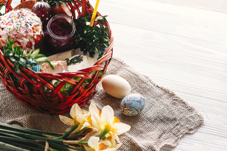 happy Easter concept. stylish basket with painted eggs, bread, ham,beets, butter on rustic wooden background with spring flowers and candle. easter food for blessing in church. Stock Photo
