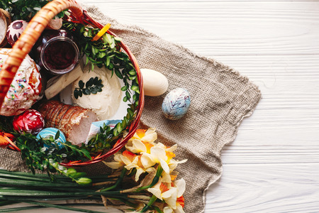 stylish basket with painted eggs, bread, ham,beets, butter on rustic wood background with spring flowers and candle, top view. easter food for blessing in church. happy Easter concept Banque d'images