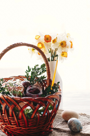 happy Easter concept. stylish basket with painted eggs, bread, ham,beets, butter on rustic wooden background with spring flowers and candle in light. easter food for blessing in church. Stock Photo