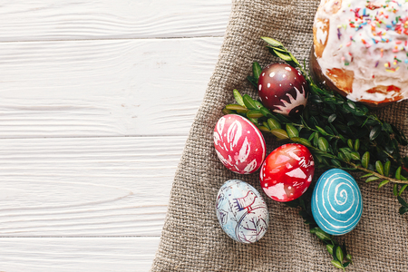 happy Easter concept. stylish painted eggs and easter cake on rustic wooden background with spring flowers, top view. seasons greeting card. space for text. modern flat lay Stock Photo - 97831182