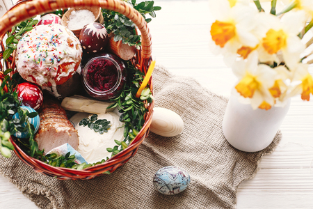 stylish basket with painted eggs, bread, ham,beets, butter on rustic wood background with spring flowers and candle, top view. easter food for blessing in church. happy Easter concept Stock Photo