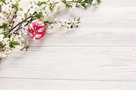 concepto de Pascua feliz. huevo pintado con estilo sobre fondo de madera rústica con flores de primavera y ramas de sauce. tarjeta de felicitación de temporadas. espacio para texto. huevos de pascua coloridos modernos