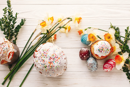 stylish painted eggs and easter cake on rustic wooden background with spring flowers, top view. space for text. happy Easter concept, modern flat lay. seasons greetings Stock Photo