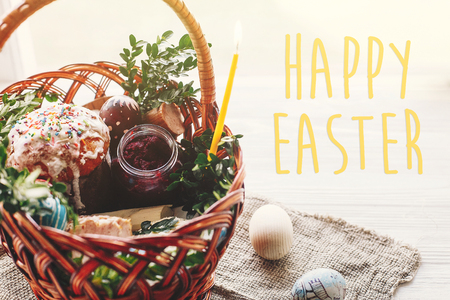 happy easter text. seasons greetings card. stylish basket with painted eggs, bread, ham,beets, butter on rustic wooden background with spring flowers and candle.