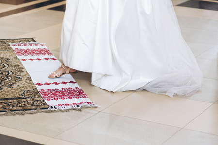 bride putting leg on traditional embroidery towel in church during holy matrimony. wedding ceremony concept