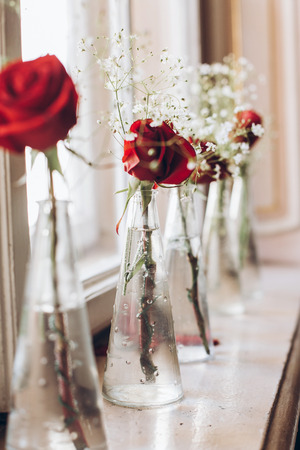 Beautiful Red Roses And White Baby Breath In Glass Vases On Table