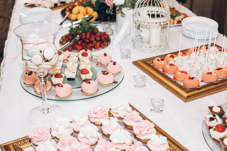 delicious candy,sweets,cupcakes,pops decorated with flowers on table at wedding reception. candy bar.