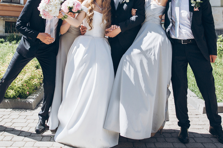 gorgeous bride with peony bouquet and stylish groom posing in sunny garden with bridesmaids and groomsmen on wedding day.