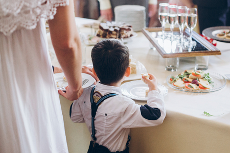 little boy eating food appetizers on table at wedding reception. luxury catering at celebrations. serving food and drinks at events concept
