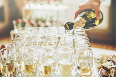 waiter pouring champagne in stylish glasses at luxury wedding reception.