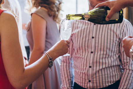 waiter pouring champagne in glass. elegant people holding glasses champagne at luxury wedding reception.