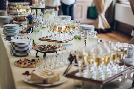 stylish champagne glasses and food appetizers on table at wedding reception. Stockfoto