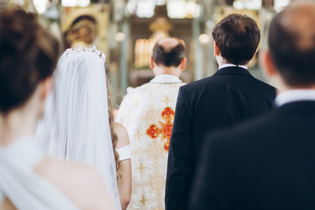 priest and groom and bride standing in church during holy matrimony. wedding ceremony concept Stock Photo