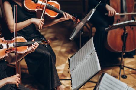 Elegante cuarteto de cuerda jugando en la habitación de lujo en la recepción de la boda en el restaurante Grupo de personas en negro tocando el violín y el violonchelo en la orquesta de teatro, concepto de música Foto de archivo