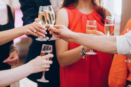 Grupo de personas elegantes con copas de champán en la boda de lujo. La gente da tostadas y anima con bebidas en eventos sociales. celebración de Navidad