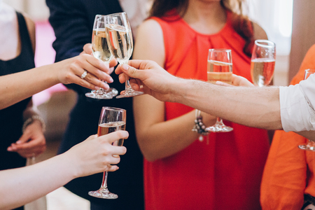 group of elegant people holding glasses of champagne at luxury wedding reception. people hands toasting and cheering with drinks at social events.  christmas celebration