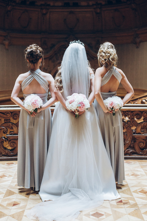 beautiful bridesmaids and bride holding stylish peony bouquets on back in the morning in hotel room. gorgeous woman in amazing silk dresses posing. wedding day