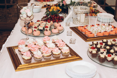 delicious candy,sweets,cupcakes,pops decorated with flowers on table at wedding reception. candy bar. tasty pink sweets for celebrations events and showers. luxury stylish catering Stok Fotoğraf - 98773665