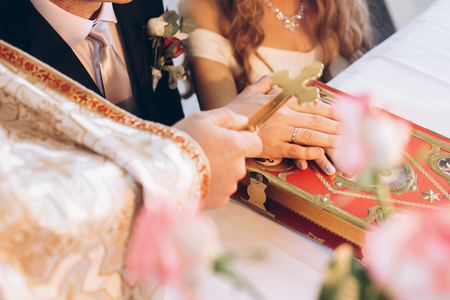 priest holding cross on groom and bride hand on bible at altar in church during holy matrimony. wedding ceremony concept
