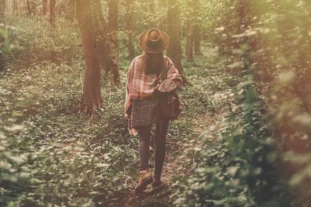 夕方の日差しの中で森の中を歩くバックパックを持つ帽子をかぶったスタイリッシュなヒップスター旅行者の女の子。日光を浴びて探検するボヘミ
