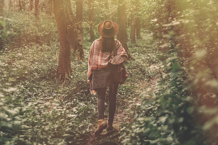stylish hipster traveler girl in hat with backpack walking in woods in evening sunshine. bohemian fashionable woman exploring in sunlight.