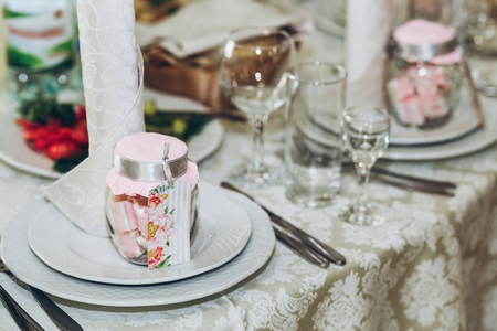 beautiful decorated setting on centerpiece table with stylish plate, glasses and cutlery at luxury wedding reception in restaurant. gift for guest. wedding favors. stylish decor and catering Banque d'images - 98773575