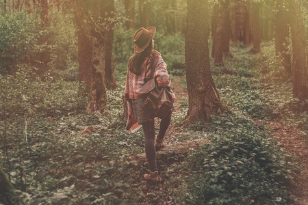 wanderlust concept. stylish hipster girl in hat with backpack walking in woods in evening sunshine. bohemian woman traveler exploring in sunlight. space for text. atmospheric moment