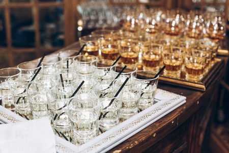stylish glasses with martini or jin with black straw on table at wedding reception. alcohol bar. tasty drinks for celebrations and events. luxury stylish catering