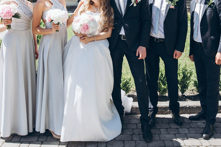 gorgeous bride with peony bouquet and stylish groom with bridesmaids and groomsmen posing in sunny garden for photo. luxury wedding couple having fun with friends