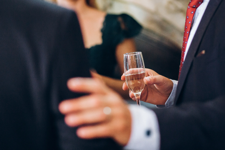 group of elegant people holding glasses of champagne at luxury wedding reception. people toasting and cheering with drinks at social events.  christmas celebration