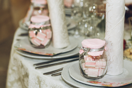 beautiful decorated setting on centerpiece table with stylish plate, glasses and cutlery at luxury wedding reception in restaurant. gift for guest. wedding favors. stylish decor and catering Banque d'images - 98773413