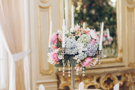 beautiful hydrangea bouquets in vases and shiny silver candelabras with candles on tables at luxury wedding reception in restaurant. stylish decor and adorning
