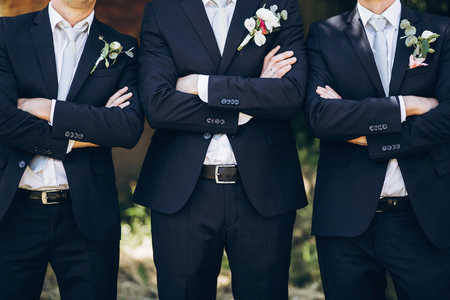 stylish groom in suit posing with groomsmen in garden on wedding day. luxury men in  rich outfits standing together. friendship